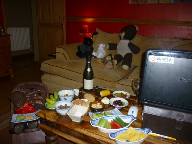 photo of Bearsac sitting on carved wooden chair next to coffee table full of party food and wine. Other teddy bears on the sofa behind