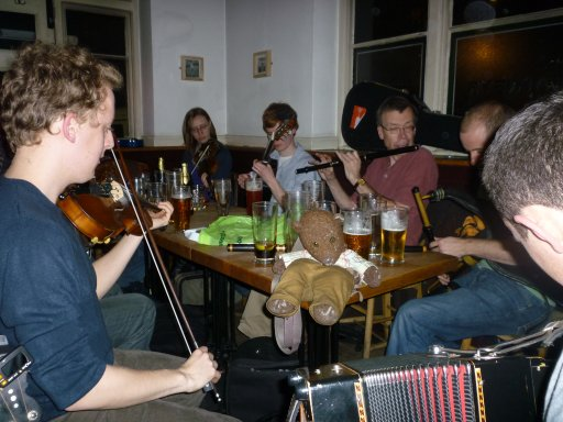 photo of bearsac with sitting on pub table amid jamming musians