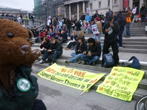 photo of Bearsac wearing Not in My Name badge with arm raised in front of protesters with banners at Trafalgar Square.